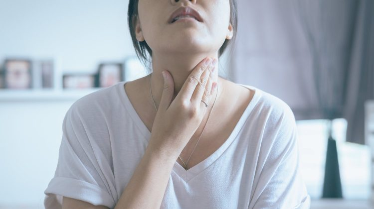 woman has sore throat female touching neck | Goiter Causes, Symptoms and Treatments | goiter | goiter thyroid | Featured