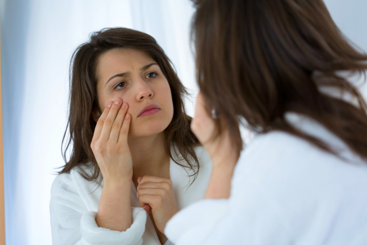 sad woman looking in the mirror touching face | Argireline: Reduce Wrinkles With Famous 'Botox in a Jar' (How It Works) | argireline | argireline serum