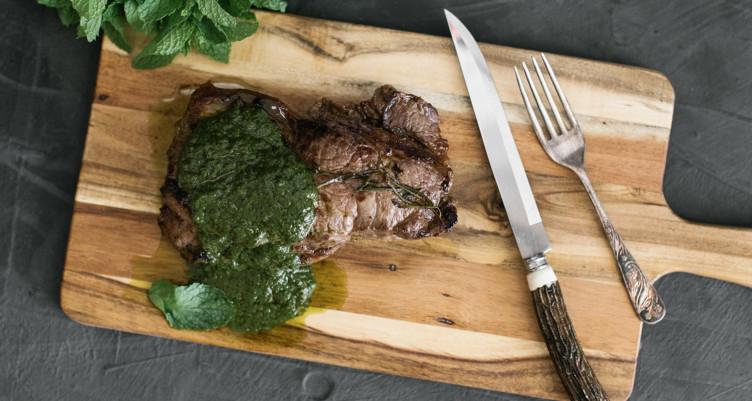 steak with chimichurri on a cutting board