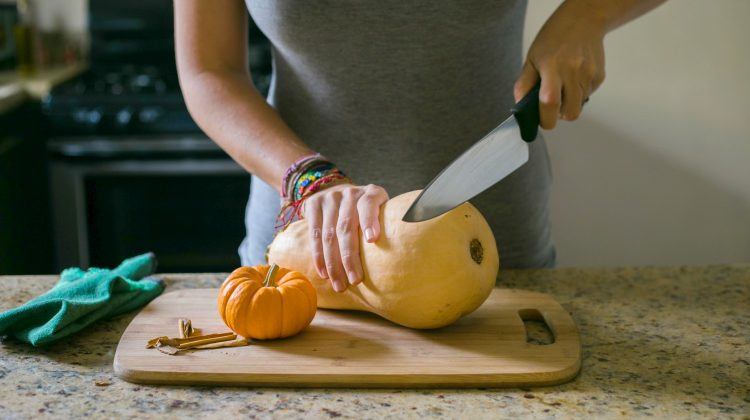 woman cutting a whole butternut squash | Healthy Fall Recipes To Make This Season | healthy fall recipes | healthy fall dinner recipes | Featured