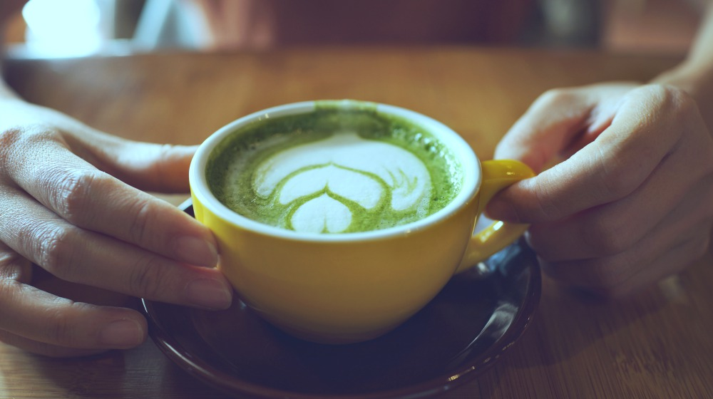 person holding cup of green tea matcha latte | Anti-inflammatory Diet Meal Plan for the Holidays | anti inflammatory diet meal plan | anti inflammatory meal plan