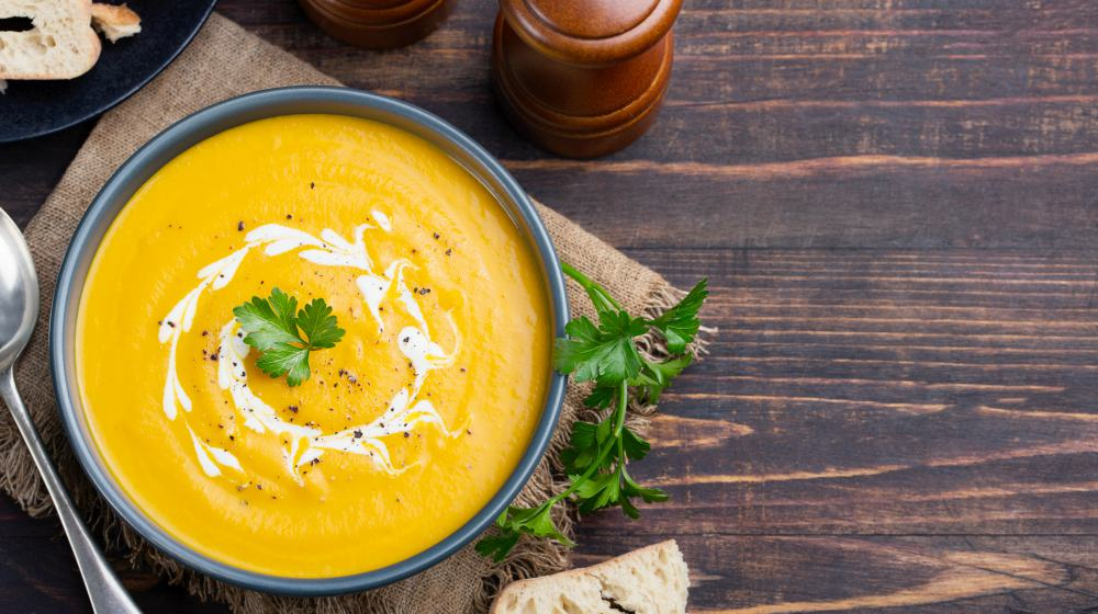 Pumpkin and carrot soup with cream and parsley on dark wooden background | Holiday Recipes To Make With Thyroid Healing Foods | thyroid healing | thyroid health