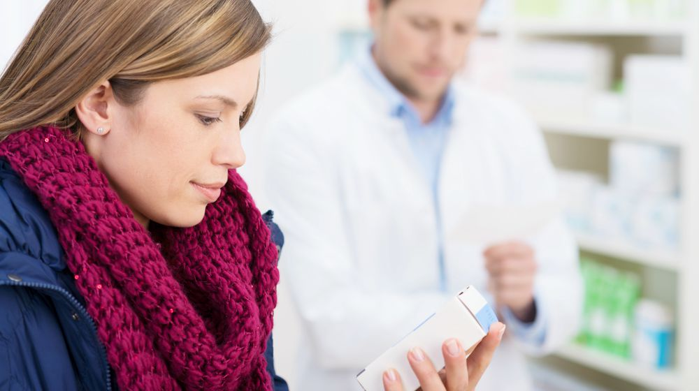 woman reading information on box of medicine | Can Synthroid Levothyroxine Cause Loss Of Appetite? [Infographic] | levothyroxine loss of appetite | does thyroid medicine make you lose weight
