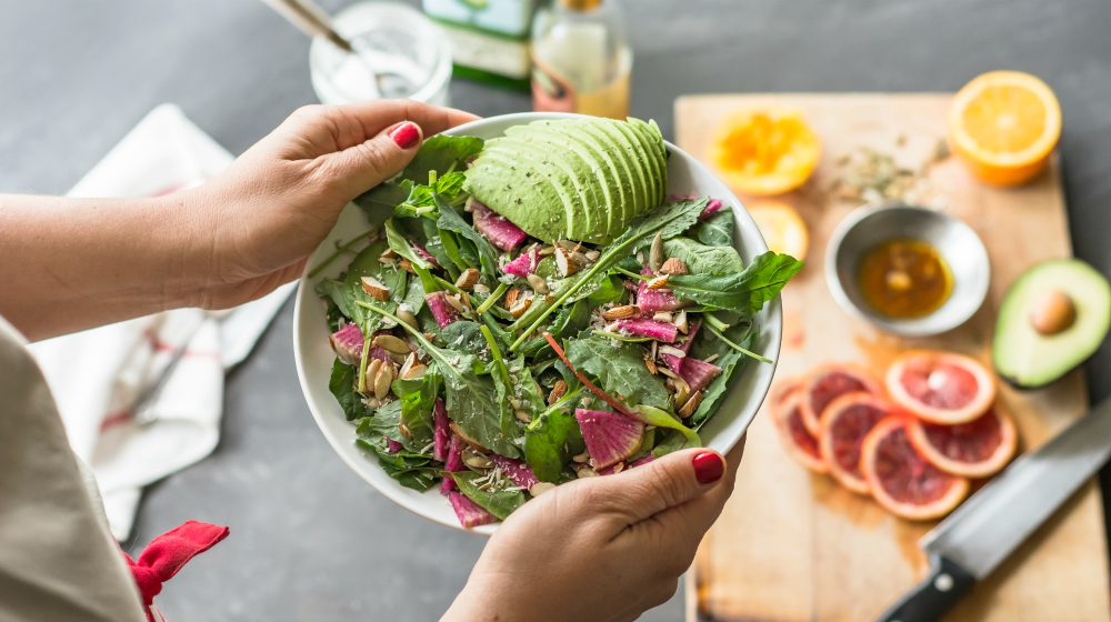 person holding fresh mixed green salad bowl | Healthy Eating Tips This Winter [INFOGRAPHIC] | healthy eating tips winter | healthy eating tips